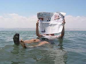 浮かびながら新聞を読む人
